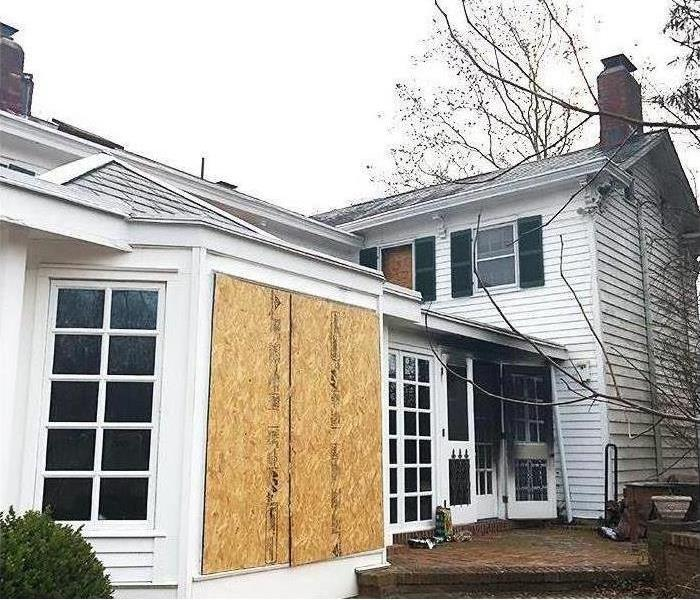Exterior view of residential fire damage with board-up windows for security and mitigation